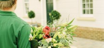 Delivery man carrying bouquet of flowers towards house